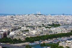 View of Paris from the Eiffel Tower. The Eiffel Tower provides a panoramic view of the Paris with the Basilica of Sacré-Cœur at the top of butte Montmartre in Stock Photography