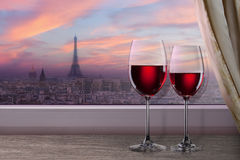 View of Paris and Eiffel tower on sunset from window. With two glasses of wine Stock Photos