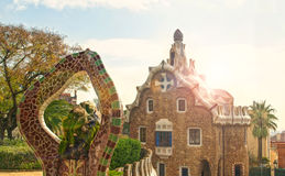 View of park and historic buildings on sunny day. View of Park Guell historic buildings with tessellated statue at front on sunny day with lens flare, Barcelona Royalty Free Stock Photos