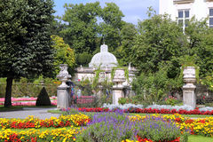 The view on the park near to building with colorful flowers in the sunny day. Stock Images