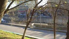 The view from the Park to auto traffic on the embankment of a city river in early spring. The view from the Park to auto traffic on the embankment of a city stock footage