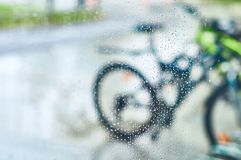 View of parked bicycles through the glass with drops of water stock photos