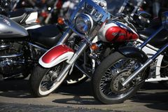 View of parked motorcycles from the sunny side. Closeup royalty free stock images