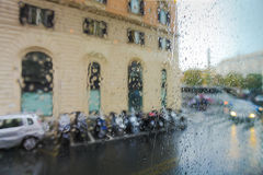 View on the parked scooters and cars on street of Rome on the rainy and  day through wet glass. Italy, Rome. Royalty Free Stock Photo