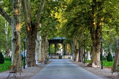 View of the famous Zrinjevac park in the city center of Zagreb, Croatia. View of the parkway or alley with old trees and the historic music pavilion, old wooden royalty free stock photography