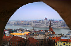View on the Parliament of Budapest through an arch. View on the Parliament of Budapest, river Danube and nearby houses on a winter day through an arch Royalty Free Stock Photo
