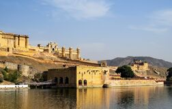 View of part of the ancient Amber fort, walls, gates and adjoining building with bridge from the Maota Lake. Jaipur, India
