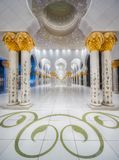 Passage of Sheikh Zayed Grand Mosque Abu-Dhabi. View of passageway at archway of Sheikh Zayed Grand Mosque with marble columns and gold decoration on them Royalty Free Stock Photo