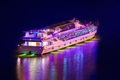 View of the passenger cruise ship is highlighted by co. The night view of the passenger cruise ship is highlighted by colored lights reflected in the water Stock Image
