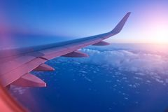 View from passenger`s seat in airplane flying above clouds in dr royalty free stock photography