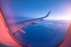 View from passenger`s seat in airplane flying above clouds in dr stock images
