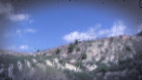 View of passing landscape from a train window after a rain intensively. Water drops sliding through the glass stock video footage