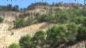 View of passing landscape from a train window after a rain intensively. Water drops sliding through the glass stock footage