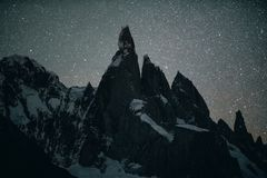 View of the peaks of the mountain of Cerro Torro and the lake in the national park of Los Glaciares during night. The stock images