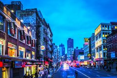View of pedestrians and traffic along Canal Street in Lower Manhattan at dusk. Royalty Free Stock Photos