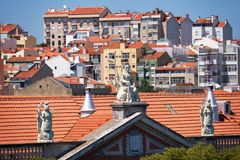 The view of pediment  decorated with sculptures on the old house. The view of Alfama houses with tile roof and pediment  decorated with sculptures on the Royalty Free Stock Photo