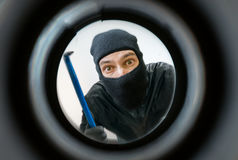 View through peephole. Thief or burglar masked with balaclava is behind the door. View through peephole. Thief or burglar masked with balaclava is holding royalty free stock photo