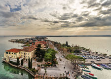 View of peninsular city of Sirmione. Sirmione, Italy - january 6, 2016: View of peninsular city of Sirmione at sunset in winter cloudy day royalty free stock images