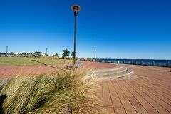 Tranquil view of Pensacola Bay along the boardwalk. This is a view of the Pensacola Bay Boardwalk which shows a bench to sit underneath a lamppost along the Stock Photos