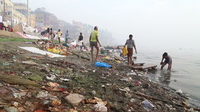 View on people going through waste at dirty shore of river Ganges. VARANASI, INDIA - 25 FEBRUARY 2015: View on people going through waste at dirty shore of stock footage