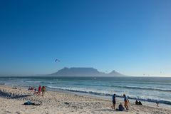 View of people and kite surfers enjoying the sun in front of Table Mountain. stock photography