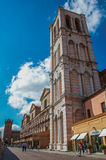 View of people and shops, in addition to the bell tower of Ferrara Cathedral. Royalty Free Stock Photos