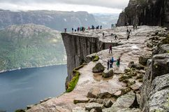 View of people walking on Preikestolen Pulpit Rock from distance with a fjord underneath royalty free stock images