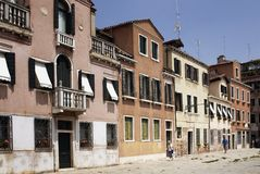 View of people walking in Venice. View of people walking in front of old, typical, historical buildings in Venice / Italy. Image shows lifestyle of the region Royalty Free Stock Photography