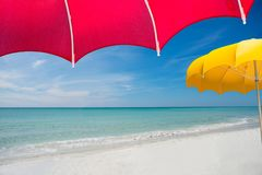 View of perfect pristine beach from under bright red umbrella royalty free stock image