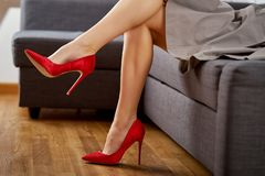 View of perfect slim and woman`s legs in red high heels against couch. View of perfect slim and woman`s legs in red high heels against gray couch stock photos