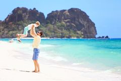 Family of two at vacation. View of perfect tropical beach and father throwing his son high up and enjoying time together during vacation at fiji Royalty Free Stock Photography