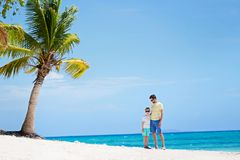Family of two at vacation. View of perfect tropical beach with palm tree and happy family of two, father and son, enjoying time together during vacation at fiji Stock Photo