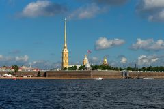 View on the Peter and Paul Fortress. RUSSIA, SAINT PETERSBURG - AUGUST 18, 2017: View on the Peter and Paul Fortress, the river Neva, the steeple with a cross Stock Photos
