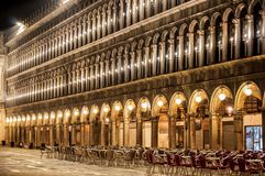Piazza San Marco building illuminated at night, with table and chairs Venice Italy royalty free stock images