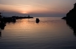 View of pier and going boat at sunset Royalty Free Stock Photography