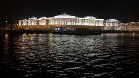 View of pier and illuminated architecture from middle of the river in night. stock video