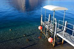 View of a pier on the lake with mountain reflection on mirror water, Lake Como, Italy.  Royalty Free Stock Images