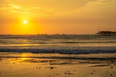 A view of the pier and the Pacific Ocean. Sunset over sea waves. Beach and stones. The rays of the sun are reflected on the sand. Pimentel Peru royalty free stock photography