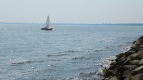 View from pier of small sailing boat floating in open sea, summer rest, sequence. Stock footage stock video