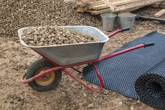 View of the piles of rubble and filled with them a construction. Wheelbarrow Stock Image