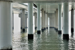 View of piles and water under bridge platform. Water surface and piles and pole of a bridge under bridge platform, shown as image feature of construction and stock photo