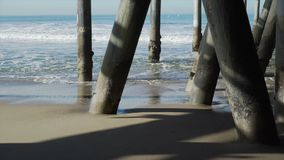View of the pilings under the Santa Monica Pier. The Santa Monica Pier is a large double-jointed pier located at the foot of Colorado Avenue in Santa Monica stock video footage