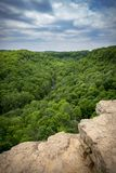 View from pinnacle of rocky cliff over lush green forest valley Royalty Free Stock Photography