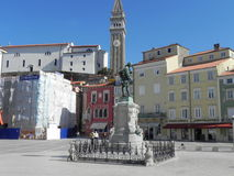 View of Pirano. The central square of Pirano in Istria with the statue of Giuseppe Tartini and the church of Saint Georg with its bell tower in the background Royalty Free Stock Photos