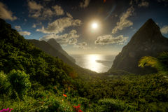 A view of the Pitons in St. Lucia. The morning sun overhead shines brightly on the ocean that sits between the two peaks of the Piton volcanic mountains in Saint Stock Photo