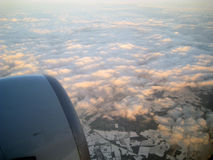 View from the plane with the engine, clouds and snowy lands. View from the plane with the engine, pink clouds and the land below Royalty Free Stock Photos
