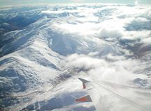 View from a plane over snow-capped mountains. A view over the wing of a plane to snow-covered mountains. The plane is above some white clouds. The peaks of the royalty free stock image