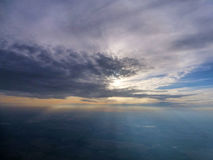 View from a plane. Sun bursting out behind the clouds, seen from a plane window Royalty Free Stock Images