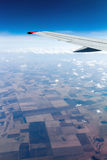 View plane window. Aerial view out of window of plane which flies above the earth surface and above clouds Stock Images