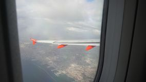 View from the plane window on Italy sea shore and buildings stock video footage